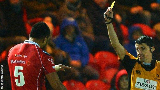 Referee Pascal Gauzere shows Maselino Paulino of Scarlets a yellow card against Northampton