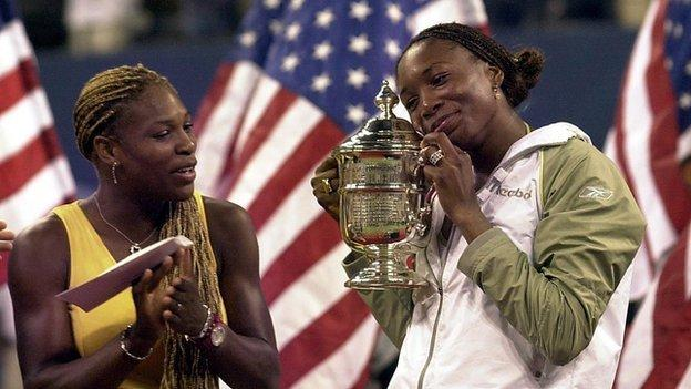 Serena Williams applauds her sister Venus who holds the 2001 US Open trophy