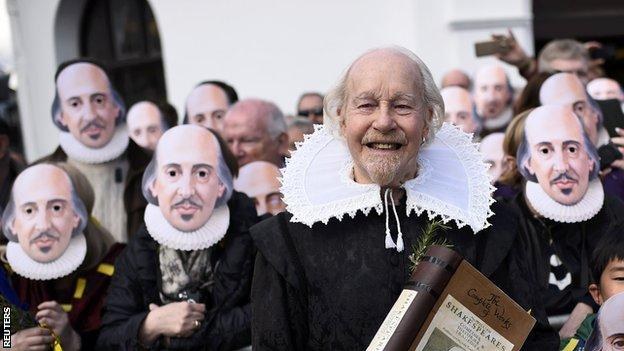 Shakespeare enthusiasts pose in masks of the Bard