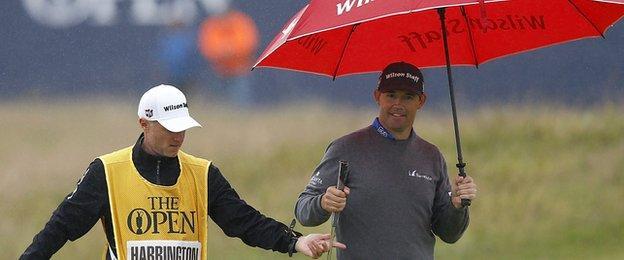 Caddie Ronan Flood hands the putter to Padraig Harrington as the rain falls at St Andrews