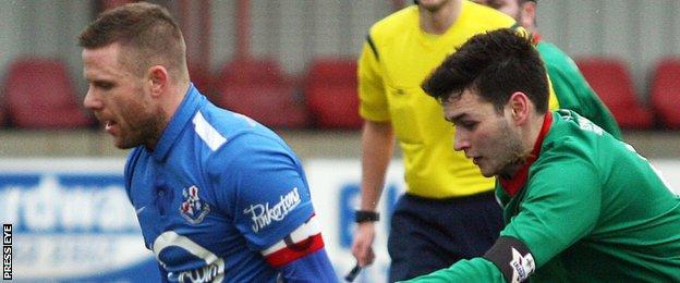 Loughgall's Steven Ferguson in action against Stuart Hutchinson of PSNI at Lakeview Park