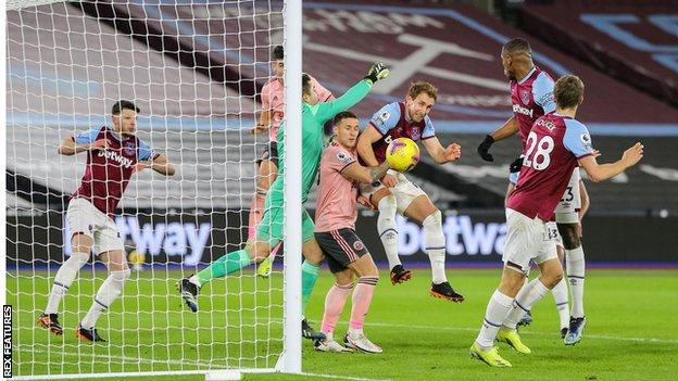 West Ham's Craig Dawson heads the ball clear of Sheffield United's Billy Sharp
