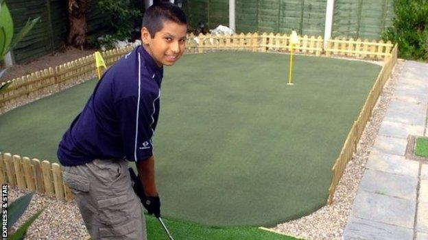 A young Rai practising on the putting green in his parents' back garden
