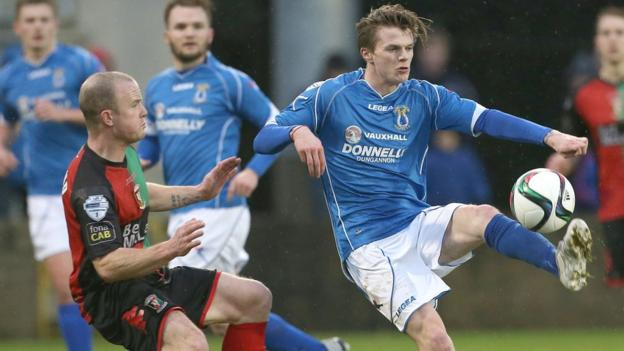 Barry Holland of Glentoran in action against Paul McElroy who scored twice in Dungannon's 3-1 home win over Glentoran
