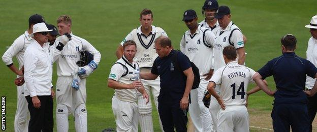 Ian Westwood receives treatment after being hit on the shoulder by a shot from Dawid Malan while fielding at short leg