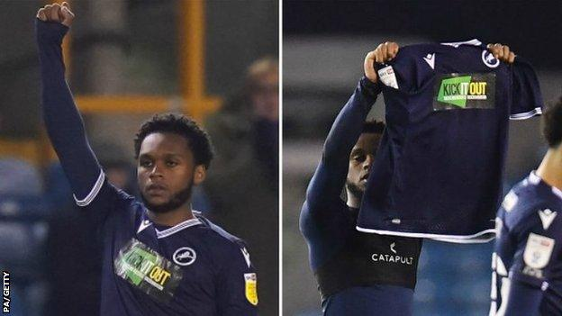 Millwall defender Mahlon Romeo raising a fist then his shirt - sponsored by Kick It Out - before and after his side's game with QPR