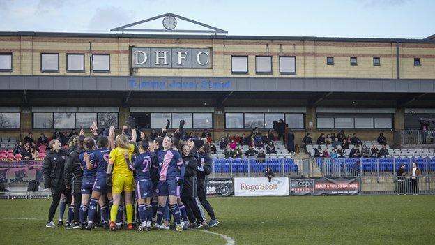 Dulwich Hamlet players celebrating in a team huddle