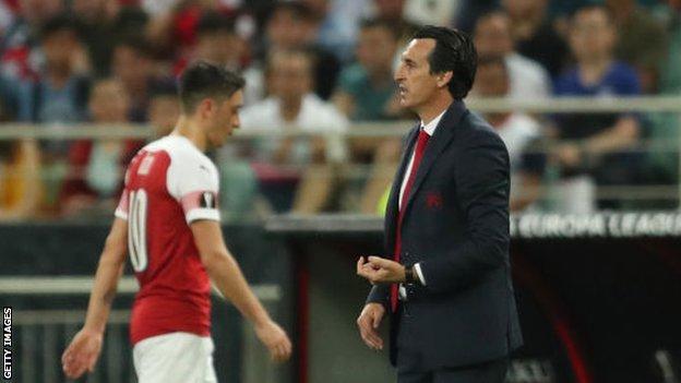 Mesut Ozil walks off the pitch past Arsenal manager Unai Emery