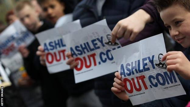 Newcastle United supporters with posters against owner Mike Ashley