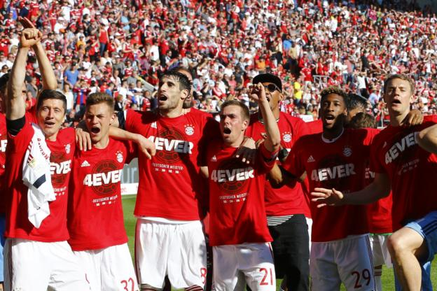 Bayern Munich's players celebrate after securing a record fourth straight Bundesliga title