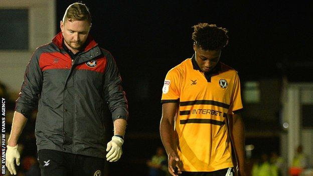 Newport striker Antoine Semenyo is escorted from the pitch after his head injury against Oxford United