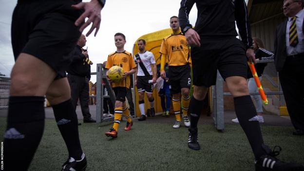 Annan and Edinburgh players enter the pitch
