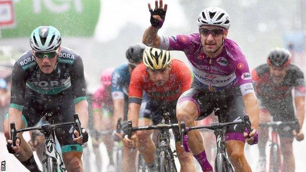 Elia Viviani celebrates victory after crossing the line on stage 17