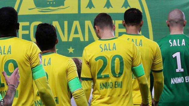 Nantes players line up wearing Sala shirts