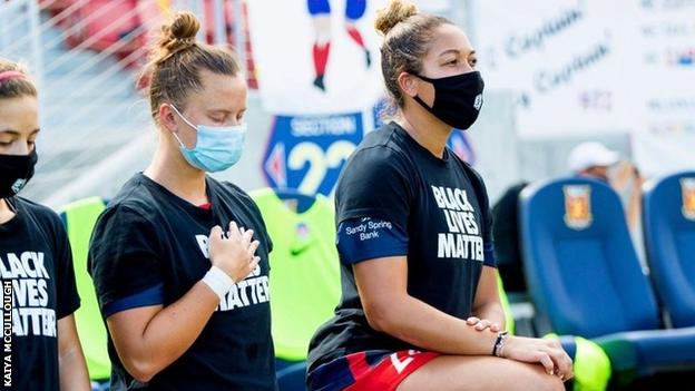 Kaiya McCullough and team-mates kneel while wearing Black Lives Matter T-shirts