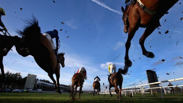 Horses clear a jump