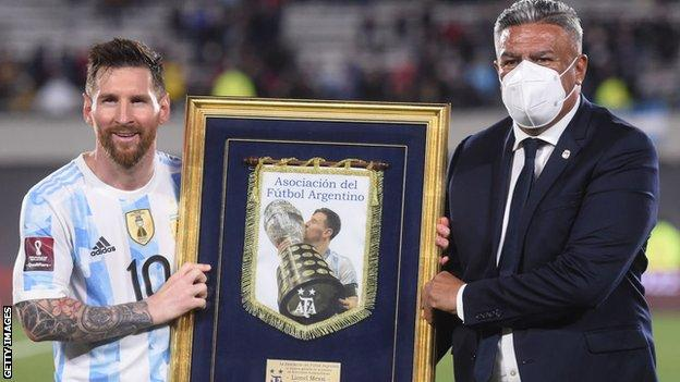 Lionel Messi (left) is presented with a recognition of his 80 goals by the president of the Argentina football association (right)
