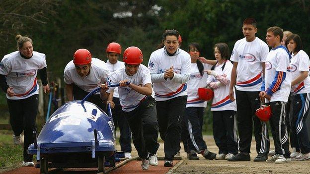 Children practice a bobsleigh start.