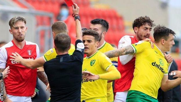 Rotherham defender Angus MacDonald (left) is sent off for a foul on Norwich midfielder Oliver Skipp