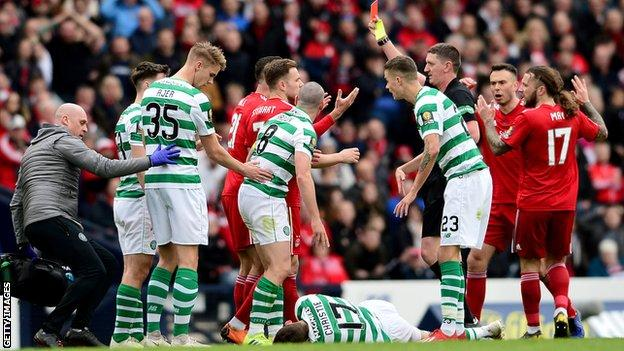 Dominic Ball is shown a second yellow card for a horrible aerial challenge on Celtic's Ryan Christie