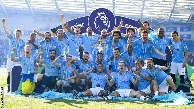 The Manchester City squad celebrate with the Premier League trophy