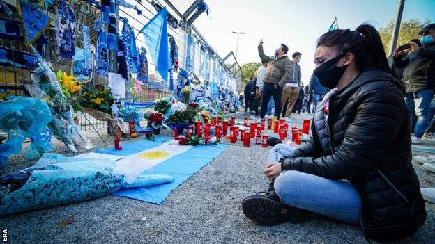 A visibly upset woman sat looking at tributes to Diego Maradona outside the San Paolo stadium