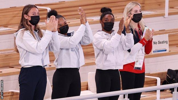 Simone Biles applauding with three team-mates