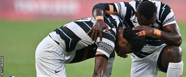 Fiji's players pray after beating New Zealand in the fina