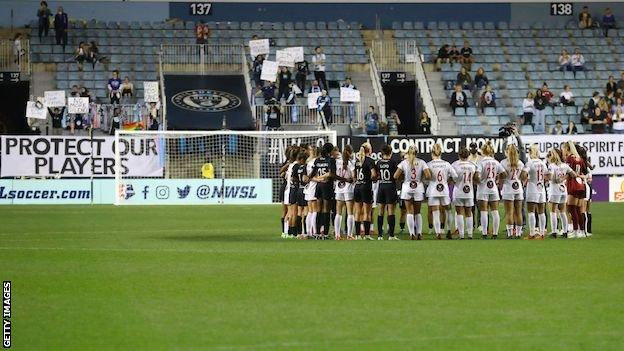 NJ/NY Gotham and Washington Spirit players arm-in-arm in a circle in a gesture of solidarity