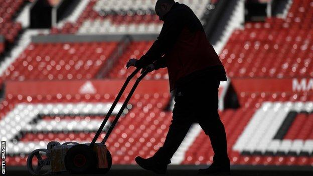 Ground staff at Old Trafford work to prepare the pitch