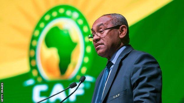 Caf president Ahmad Ahmad speaks on stage next to confederation logo