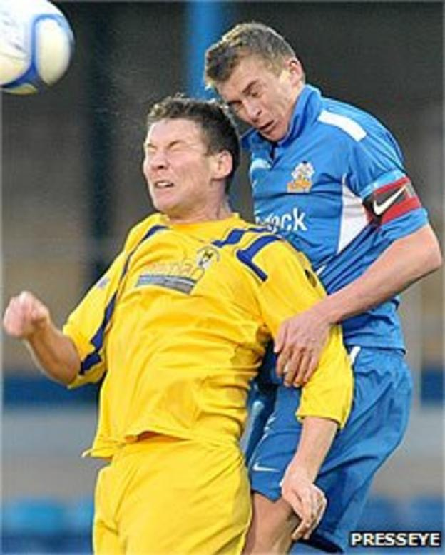 Dungannon's Alain Emerson is beaten in the air by Jay Magee of Glenavon