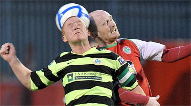 Stephen McAlorum of Donegal Celtic competes for a high ball with Cliftonville's Ryan Catney
