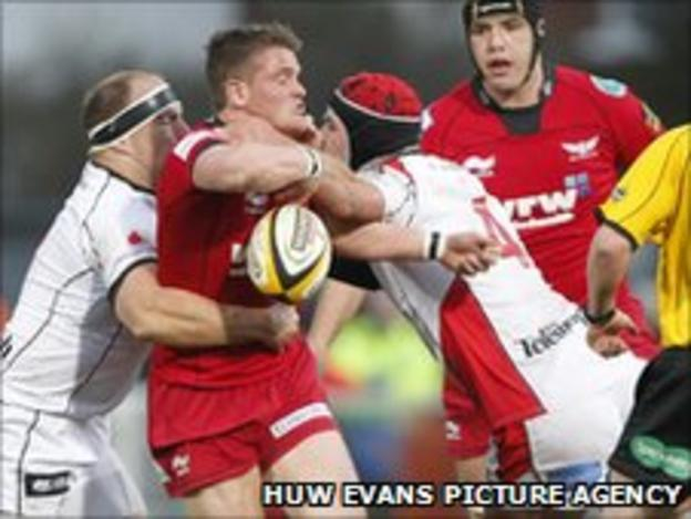 Scarlets' Tavis Knoyle is tackled during the game at Ravenhill