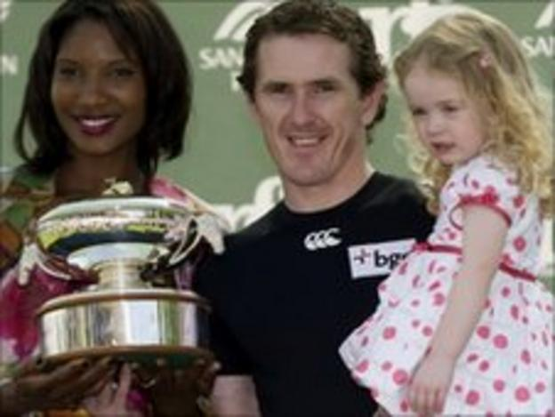 Denise Lewis presents the champion jockey trophy to Tony McCoy, with daughter Eve