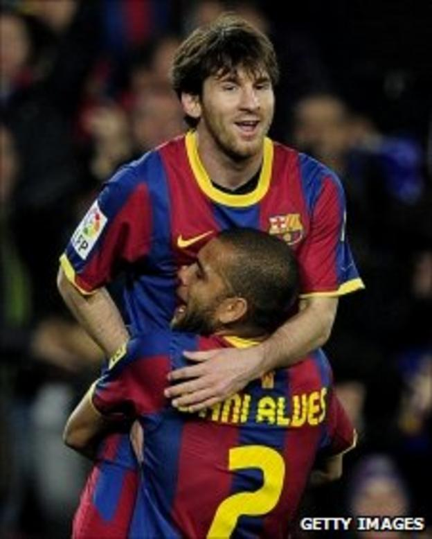 Messi (back) celebrates his 50th goal of the season with team-mate Dani Alves