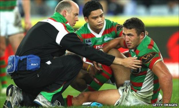 Sam Burgess is tended to after injuring his ankle