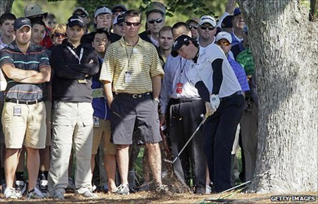 Rory McIlroy plays out from beside a tree on the 16th on the first day of the Wells Fargo Championship