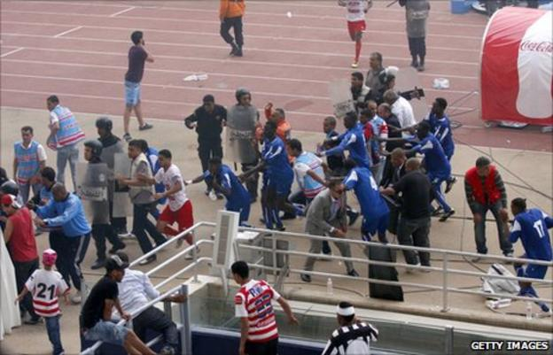 Players of Al Hilal run for shelter after being attacked by Club Africain fans during an African Champions League game