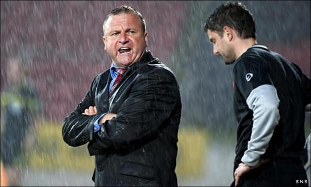 Billy Reid is caught in the McDiarmid Park downpour