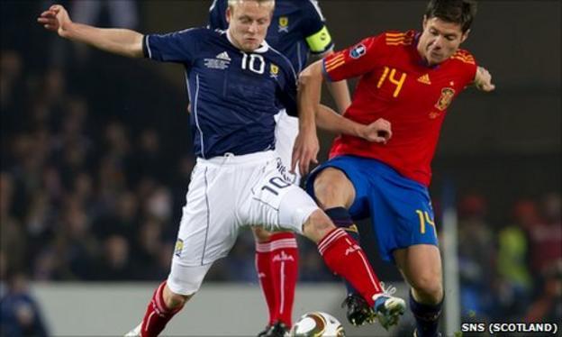 Steven Naismith challenges Spain midfielder Xabier Alonso