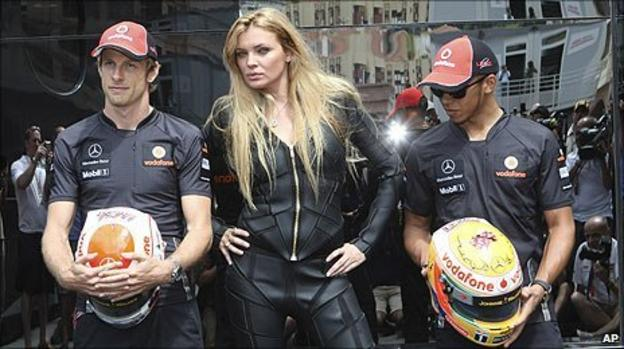 Jenson Button and Lewis Hamilton pose with their new helmets and a model in Monaco