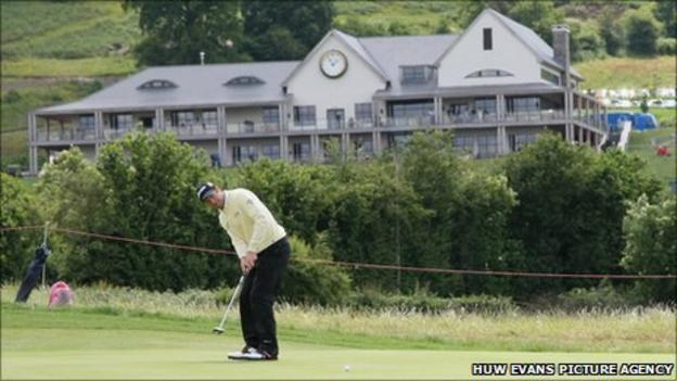 Bradley Dredge makes a putt in the shadow of the Celtic Manor clubhouse