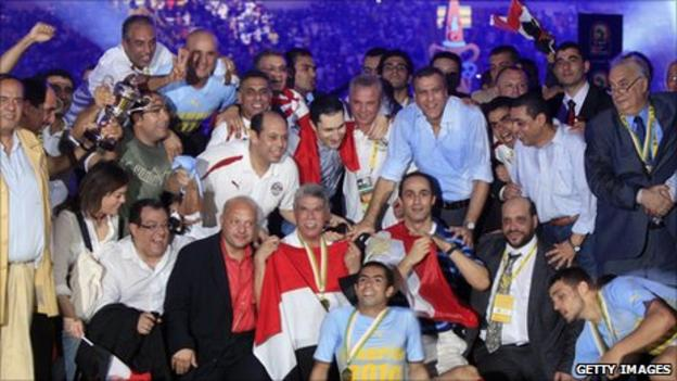 The sons of Egyptian president Hosni Mubarak (half-right, standing and crouching) celebrate winning the Nations Cup in 2010 with the national team