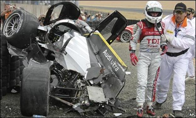Allan McNish is led from his crashed Audi