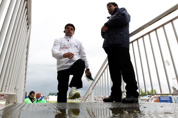 Umpire Alim Da leaves the field after one of numerous pitch inspections on a rain-disrupted day at the Rose Bowl