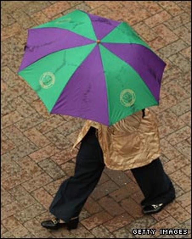 An official sports a Wimbledon umbrella