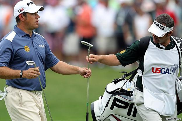 Lee Westwood takes hold of his putter on the first