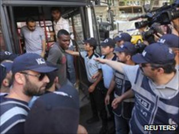 Nigerian footballer Emmanuel Emenike disembarks from a police vehicle in Turkey