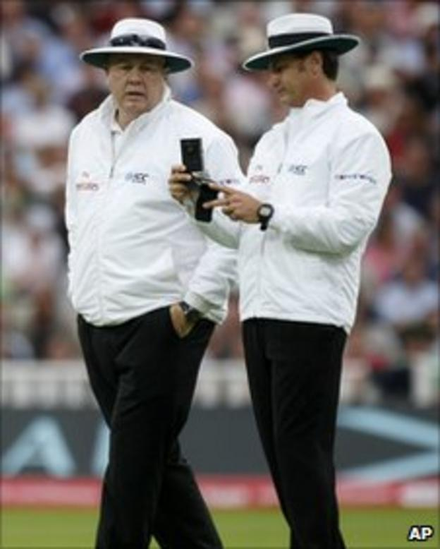 Umpires Steve Davis and Simon Taufel consult their light meters